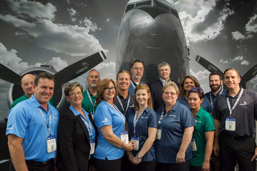 Aereos, Atlas Aerospace, ACP and EulessAero staff pose in the family company booth during last year's MRO Americas 2016. The 2016 booth featured a Douglas DC-3 aircraft. What airplane will we feature this year? Come and find out and enter to win an Apple Watch.