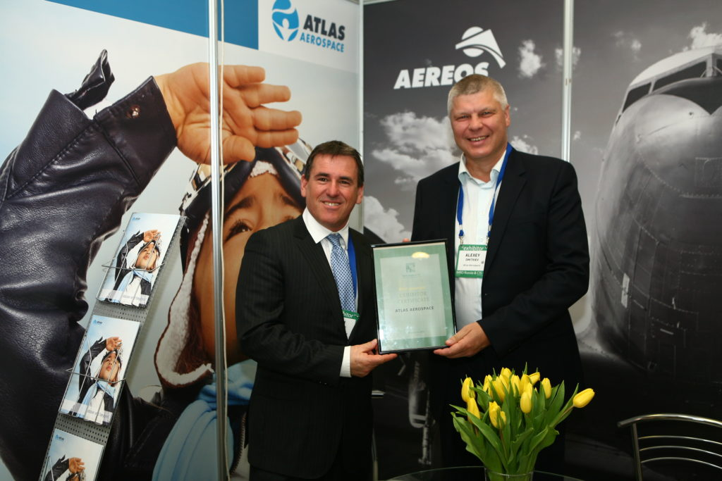 Atlas associates, Haim Gettler and Alexey Dmitriev are showcasing the Atlas' MRO Russia & CIS award certificate with the Atlas booth as the backdrop.
